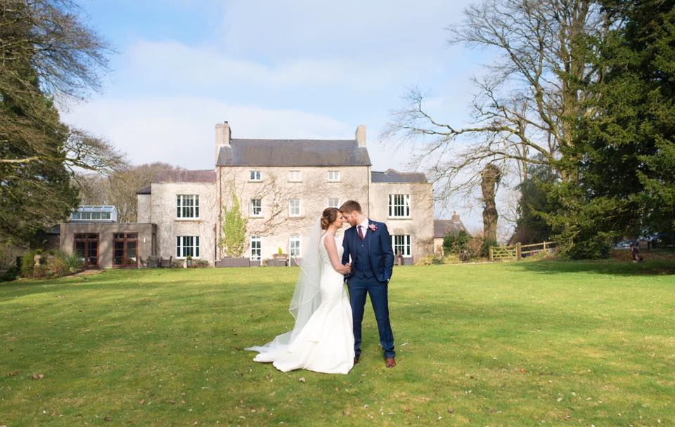 A married couple standing in the Fairyhill grounds with the Georgian house in the background.