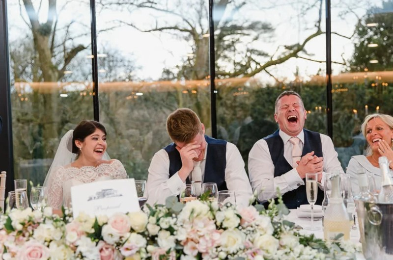 Bride, groom and the groom's parents laughing at a joke in the K Room at Fairyhill