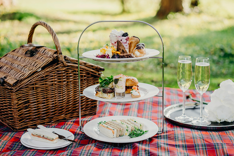 An image of an afternoon tea picnic flanked by a wicker hamper and glasses of champagne.