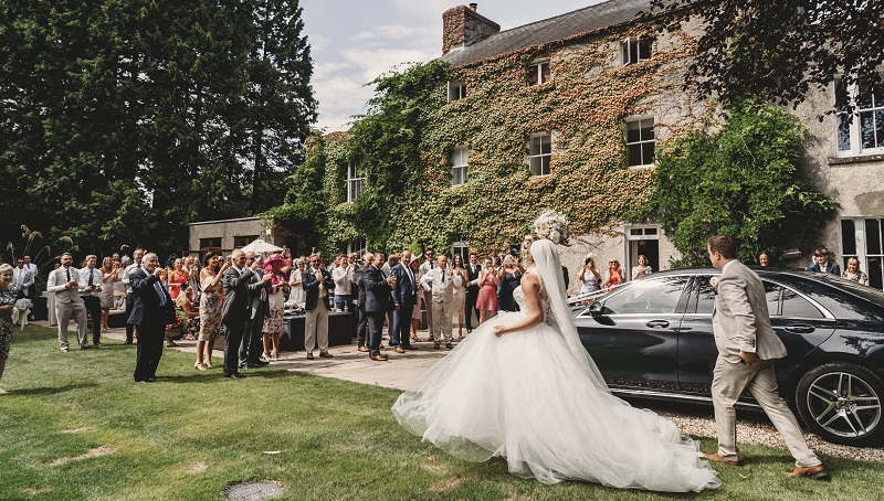 Bride and groom arriving at Fairyhill for outdoor reception