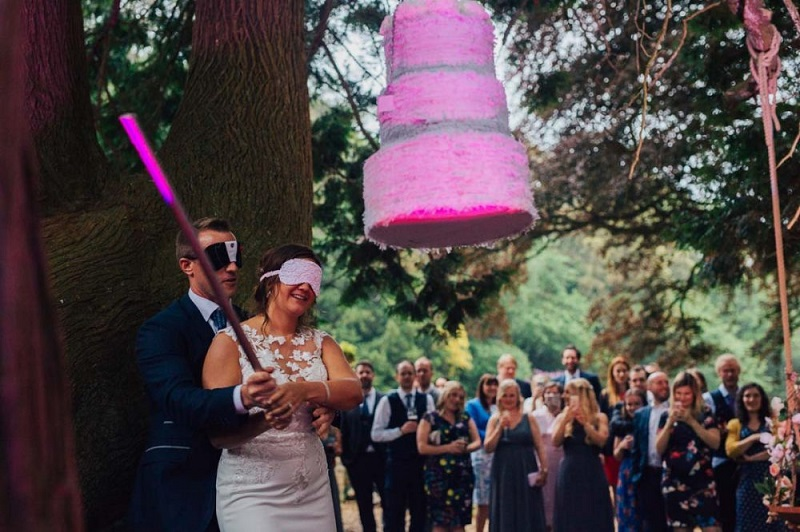 Bride and groom hitting a pinata hanging from a tree