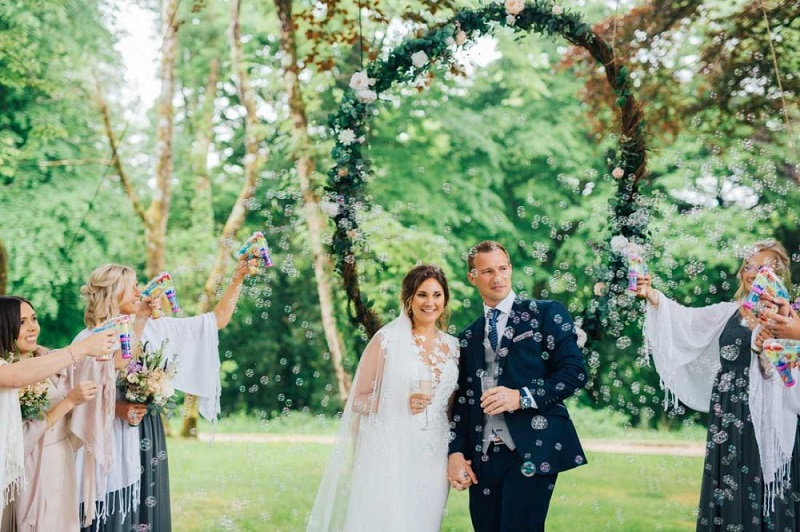 Bride and groom showered with bubbles during outdoor wedding ceremony