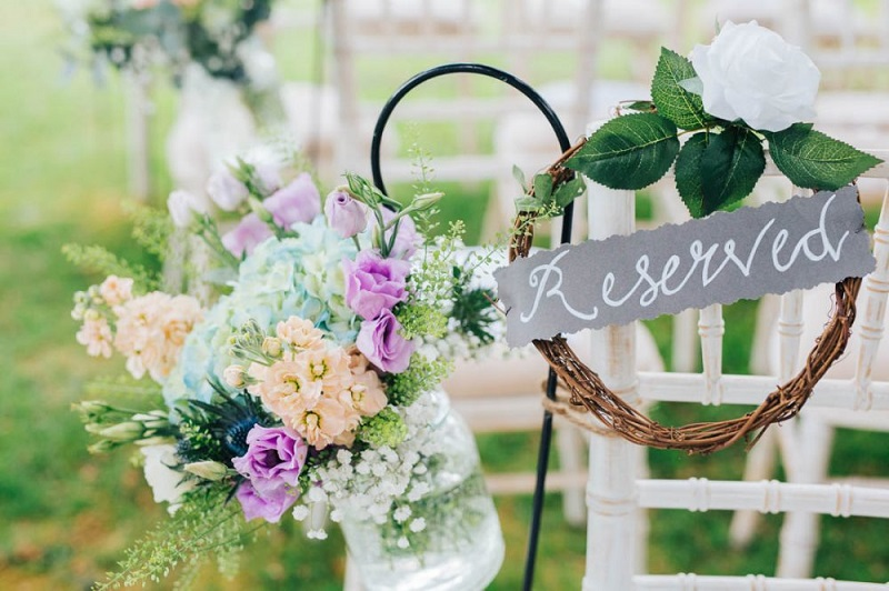 Floral display and reserved sign at outdoor wedding