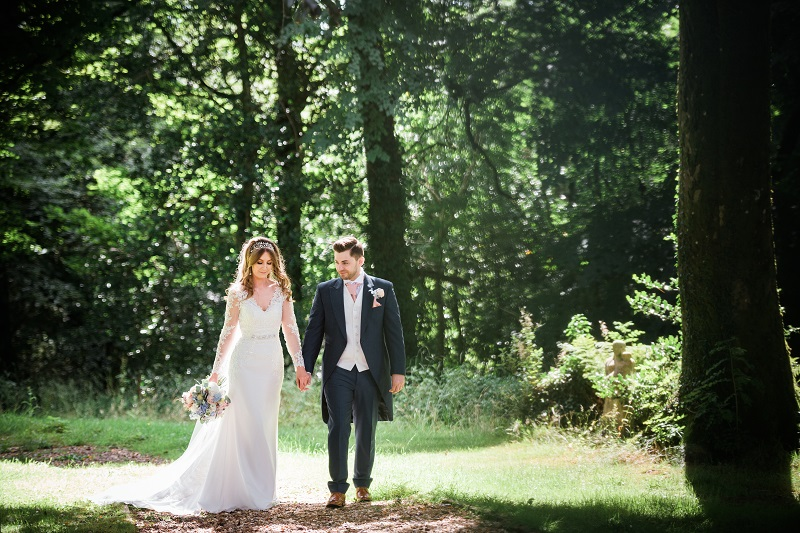 An image of a bride and groom holding hands and walking through the woods near wedding venue Fairyhill.