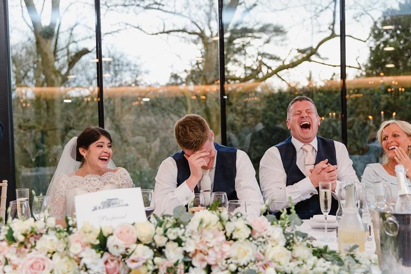 An image of a bride and groom seated next to the groom's parents laughing at the best man's speech