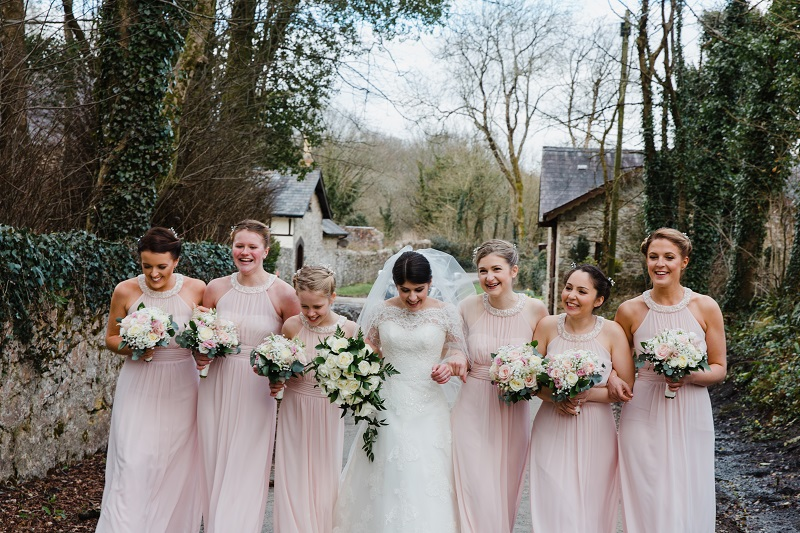 An image of a bride and 6 bridesmaids with arms linked walking down a country lane