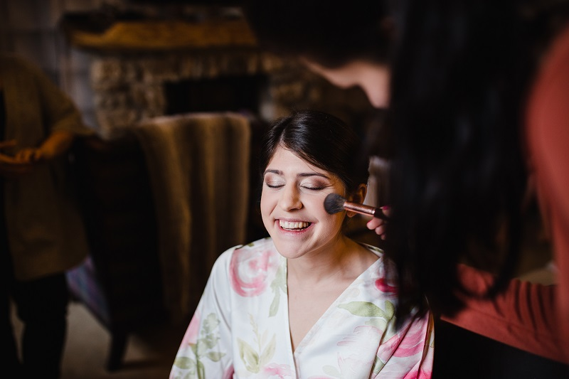 An image of a woman in a robe having makeup applied to her face