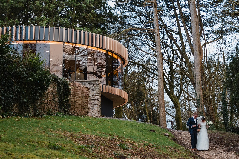 An image of a bride and groom walking down a path near the newly constructed K-Room at Fairyhill
