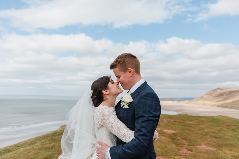 A bride and groom holding each other on top of a cliff with the sea in the background