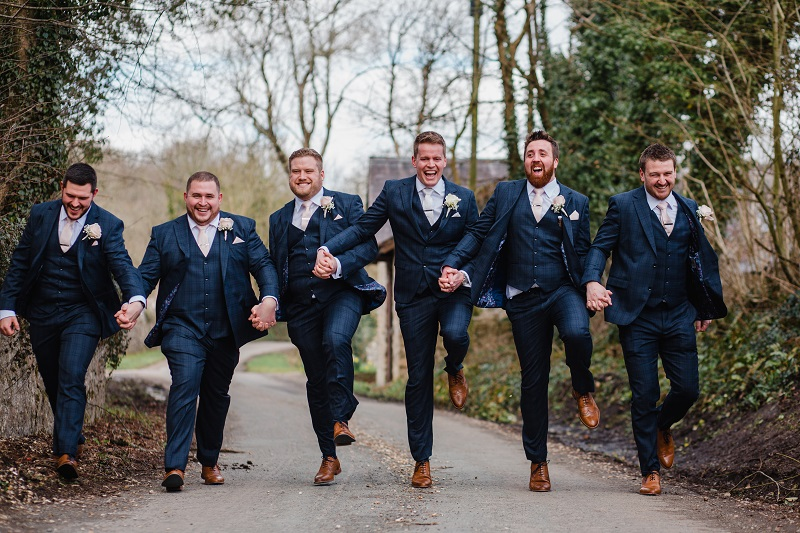 A groom and 5 groomsmen holding hands whilst skipping along a country lane
