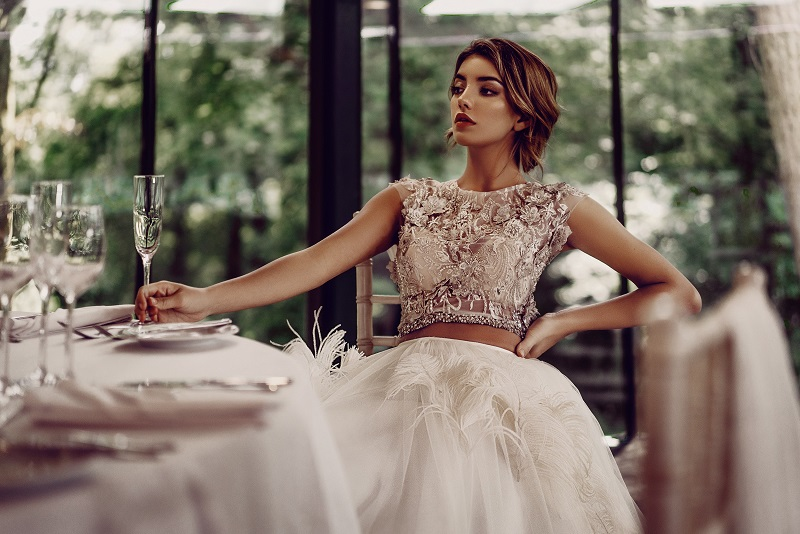 A model sitting at a table in the K Room wearing a wedding dress designed by Stephanie Allin