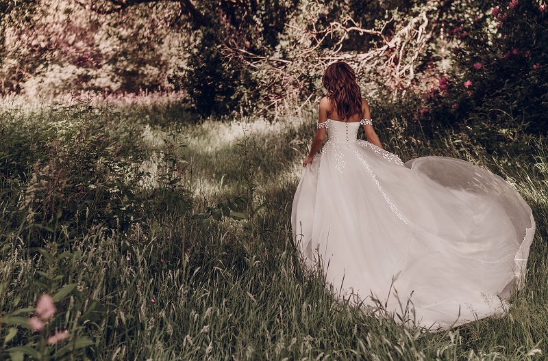 A model wearing a wedding dress designed by Stephanie Allin in the woodlands at Fairyhill