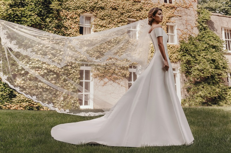 Side view of a model wearing a Stephanie Allin wedding dress next to the Georgian mansion at Fairyhill