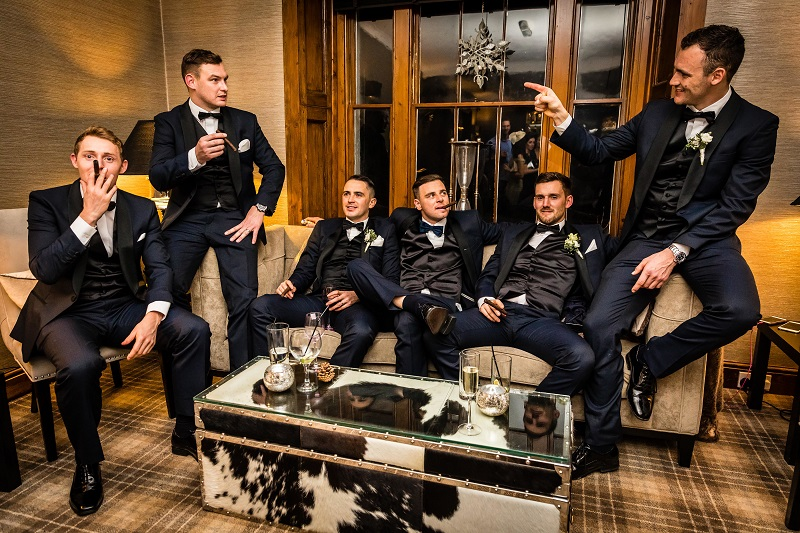 An image of men in wedding tuxedos, sitting on a sofa, smoking cigars.