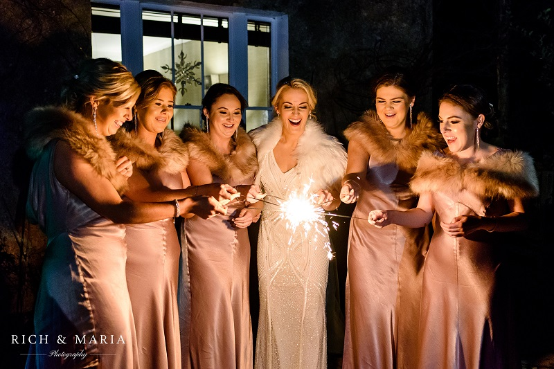 A group of women at a winter wedding playing with sparklers.