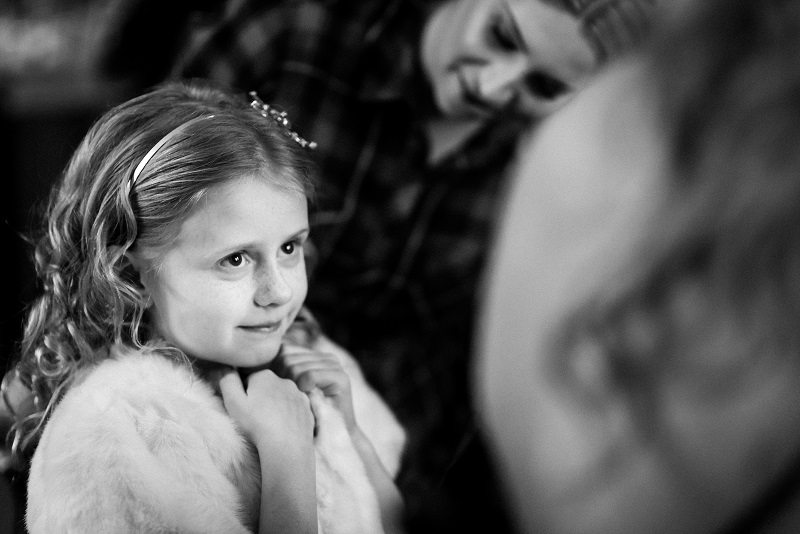 A black and white image of a young girl at a winter wedding.