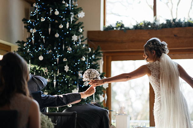 Bride handing a guest a wedding bouquet at a Christmas themed wedding